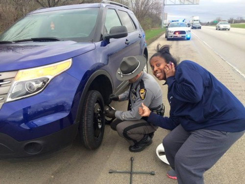 Black woman getting help changing tire from policeman