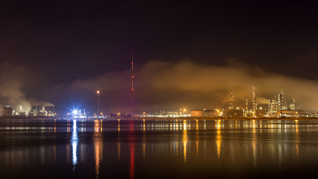 Smokestacks from factories near a large body of water.